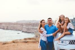 Familie im Mietwagen am Meer