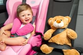 Kind in Kindersitz mit Teddy