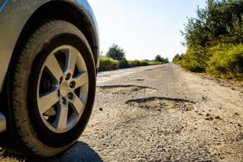 Mietwagen mieten und in die Ukraine fahren - Auto auf beschädigter Straße