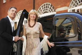 Paar im Luxuswagen zur Oper