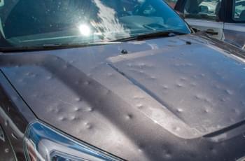 Hagelschade auf der Motorhaube beim Mietwagen