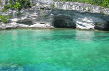 Türkisblaues Wasser vor Kalksteinhöhlen