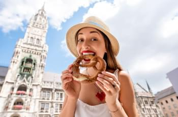 Young female tourist holding traditional bavarian bread
