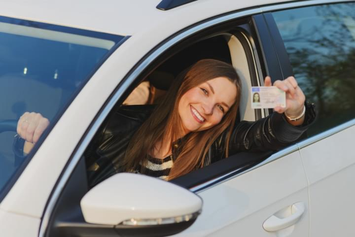 Junge Frau zeigt geeigneten Führerschein für den Mietwagen ab 18