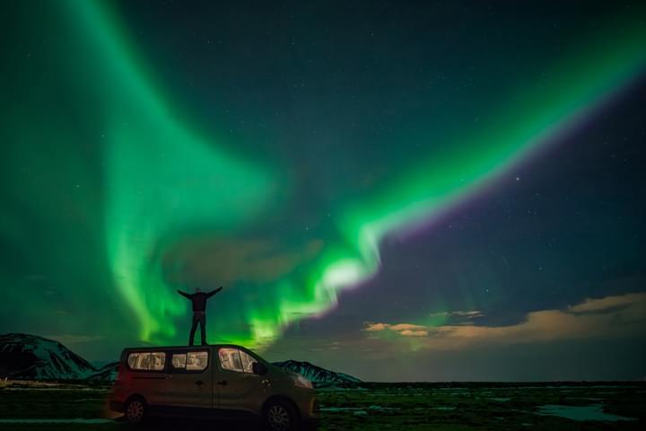 Homme sur la voiture devant les aurores boréales
