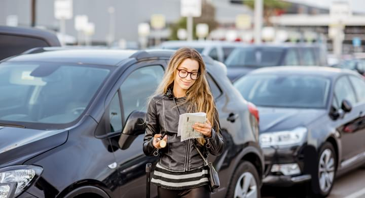 Woman in front of a rental car