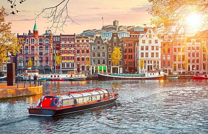 Kanaal met boot in Amsterdam bij zonsondergang
